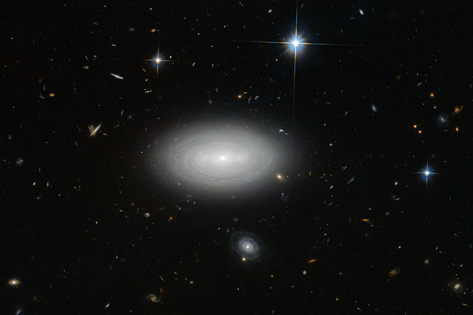 Only three local stars appear in this image, quartered by right-angled diffraction spikes. Everything besides them is a galaxy; floating like a swarm of microbes in a drop of water, and brought into view here not by a microscope, but by the Advanced Camera for Surveys on the Hubble Space Telescope. In the foreground, the spiral arms of MCG+01-02-015 seem to wrap around one another, cocooning the galaxy. The scene suggests an abundance of galactic companionship for MCG+01-02-015, but this is a cruel trick of perspective. Instead, MCG+01-02-015's unsentimental naming befits its position within the cosmos: It is a void galaxy, the loneliest of galaxies. The vast majority of galaxies are strung out along galaxy filaments — thread-like formations that make up the large-scale structure of the Universe — drawn together by the influence of gravity into sinuous threads weaving through space. Between these filaments stretch shallow but immense voids; the Universe's wastelands, where, outside of the extremely rare presence of a galaxy, there is very little matter — about one atom per cubic metre. One such desolate stretch of space is what MCG+01-02-015 reluctantly calls home. The galaxy is so isolated that if our galaxy, the Milky Way, were to be situated in the same way, we would not have known of the existence of other galaxies until the 1960s.
